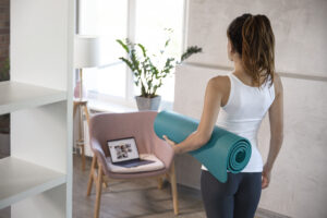 A young slim woman with a beautiful figure in a sports uniform is preparing for online fitness training at home with laptop and fitness mat. Online training, online fitness, stay home, quarantine, online training.