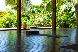 Open tropical yoga studio place with view outside to the beautiful garden with palm trees and ocean. Holiday concept.